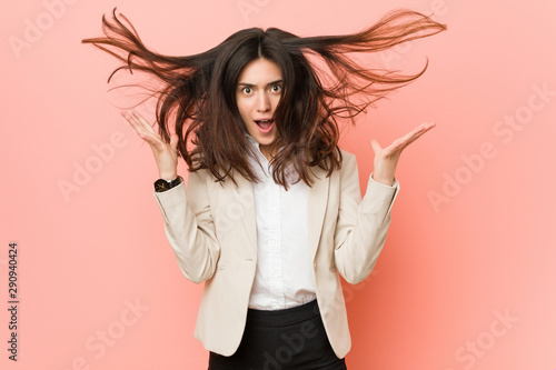 Photo  Young brunette business woman against a pink background celebrating a victory or success, he is surprised and shocked