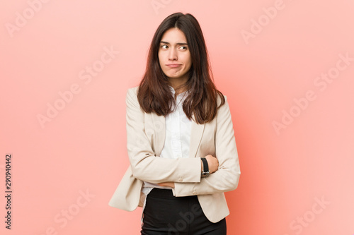 Pinturas sobre lienzo  Young brunette business woman against a pink background unhappy looking in camera with sarcastic expression