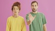 Attractive serious young couple making stop gesture with hands and shaking their heads negatively over pink background isolated