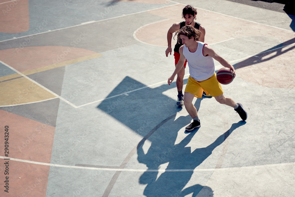 Fototapety, obrazy: Top view of two young sporty men playing basketball on playground in morning .