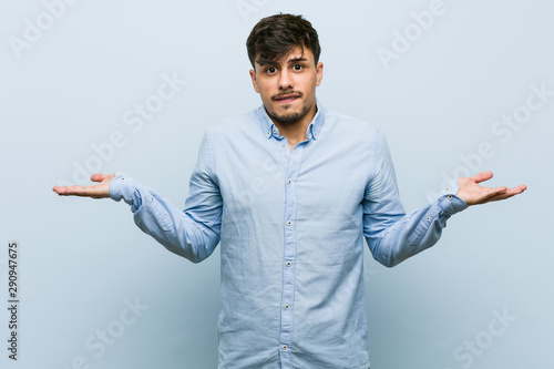 Fotografie, Obraz  Young hispanic business man confused and doubtful shrugging shoulders to hold a copy space