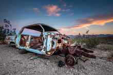 Close Up Of A Wrecked And Rusty Car, Abandoned In Rhyolite Ghost Town In Death Valley, Under A Colorful Sky At Sunset