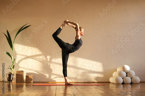 Obraz Beautiful woman doing yoga at sunset time in a studio - fototapety do salonu