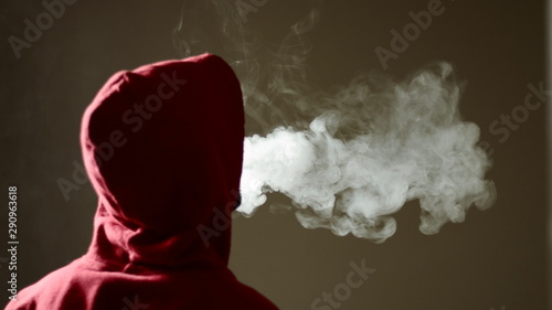 Photo Young male in red hoodie vaping smoking, exhales thick vapor, isolated rear view