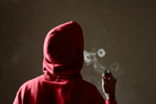 Young Male In Red Hoodie Vapin...