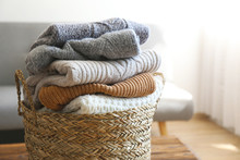 Bunch Of Stacked Knitted Pastel Color Sweaters With Different Knitting Patterns Perfectly Folded In Wicker Basket On Table, Living Room Background. Fall Winter Season Knitwear. Close Up, Copy Space.