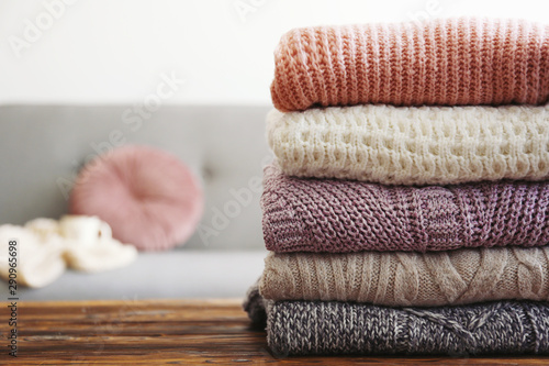 Fototapeta Bunch of knitted pastel color sweaters with different knitting patterns perfectly folded in stack on brown wooden table, white brick wall background. Fall winter season knitwear. Close up, copy space obraz