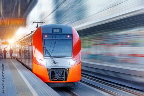 Obraz Passenger electric train arrives at the station in urban landscape. - fototapety do salonu