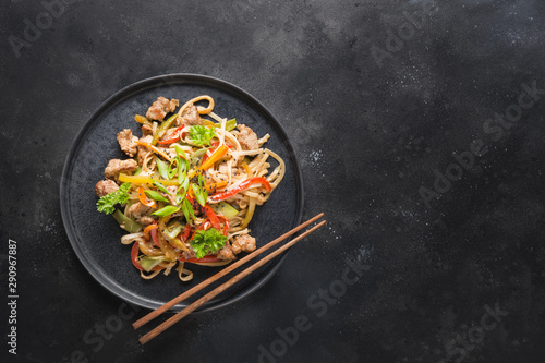 Cuadros en Lienzo  Udon stir-fry noodles with pork bowl and vegetables on black stone background
