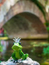 Ceramic Frog With Crown In Garden Next To River