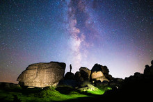 Silhouette Of Figure Stargazing In Rocky Landscape Below A Clear Night Sky & Vibrant Milky Way, Dartmoor National Park, UK