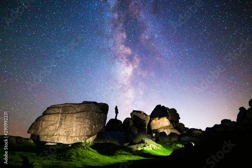 Silhouette of figure stargazing in rocky landscape below a clear night sky & vib Wallpaper Mural