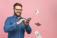 Portrait Of Attractive Handsome Reckless Careless Carefree Guy Wearing Jeans Shirt Throwing Money Away Wealth Isolated Over Pink Background.