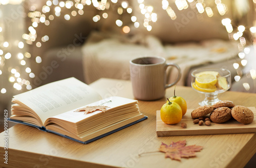 obraz lub plakat hygge and cozy home concept - book, autumn leaves, cup of tea with lemon, almond nuts and oatmeal cookies on table