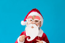 Funny Child Dressed Santa Claus Costume Against Blue Background