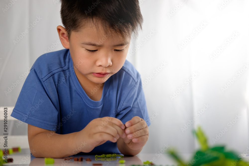 Fototapety, obrazy: Cute asian boy is playing with blocks from toy constructor with