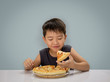 Asian 6-7 year boy is happy to eating pizza with a hot cheese me