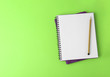 Leinwanddruck Bild - Notebooks with pencil on light green background, top view. Space for text