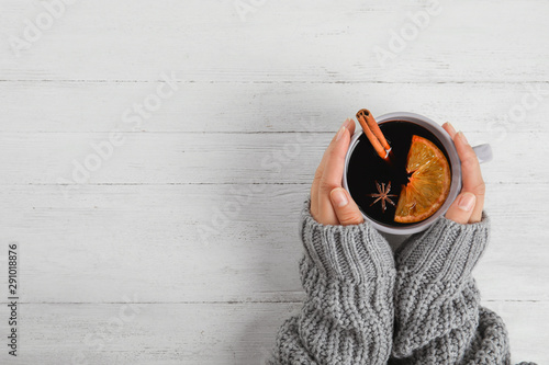 Papiers peints Cafe Woman holding cup of hot mulled wine at white wooden table, top view with space for text. Winter drink