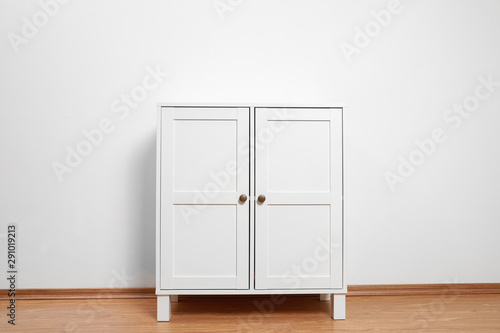 Fotomural Wooden cabinet near white wall. Stylish home furniture