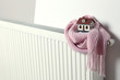 Leinwandbild Motiv House model wrapped in pink scarf on radiator indoors, space for text. Winter heating efficiency