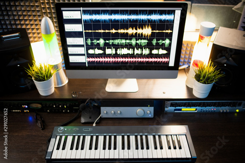 Piano keyboard and computer screen with waveform sound visualization on desk - 291027652