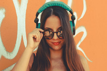 Young Attractive Girl Looking At Camera While Listen Music