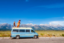Woman In Dinosaur Costume With A Camper Van In The Grand Tetons