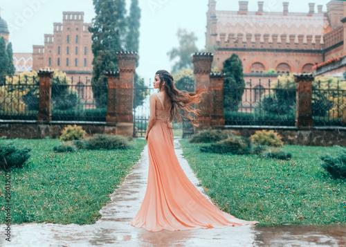 Samotna Atrakcyjna brunetka kobieta idzie w deszczu w pobliżu zamku stojana. Młoda księżniczka w różowej mokrej sukience z pociągiem. Trzepoczące włosy, latające na wietrze. Jesień smutny krajobraz.