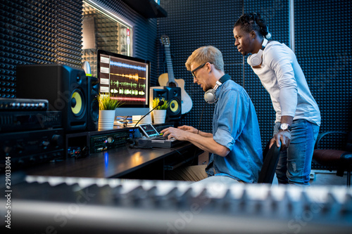 One of young musicians pressing pianoboard keys with colleague standing near by - 291033014