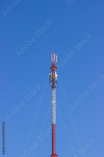 Red and white Telecommunication tower in a day of clear blue sky.