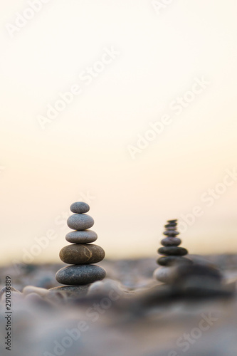 Aluminium Prints Stones in Sand Balanced stone pyramid on pabbles beach with sunset. Zen rock, concept of balance and harmony.