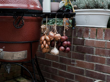 Onions And Garlic Hanging From A Bbq In An English Country Garden
