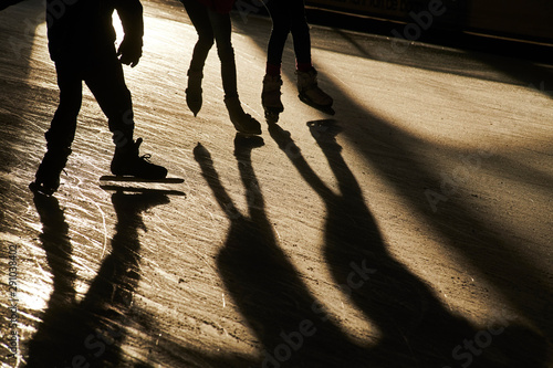 Silhouettes of people on ice skates in cold winter sunshine