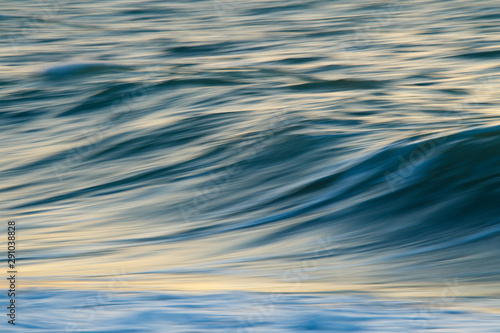 Waves in the motion during sunset, smooth abstract background. Fototapet