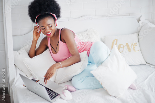 Young african american woman sitting in bed while working on laptop and listen music on earphones. - 291040453