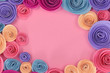 Pastel blue, pink, yellow and violet paper craft rose flat lay background with flowers around the endges and empty copy space in middle