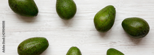 Whole avocados on a white wooden surface, top view. Overhead, from above. - 291048008