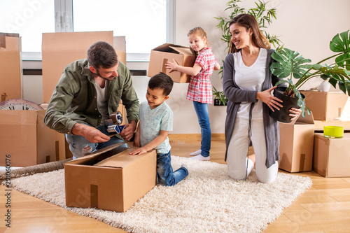 Fototapeta Young couple moving in a new home with their children helping them obraz