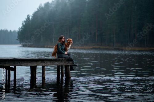 Photo girl with a dog sit on a pier on the lake