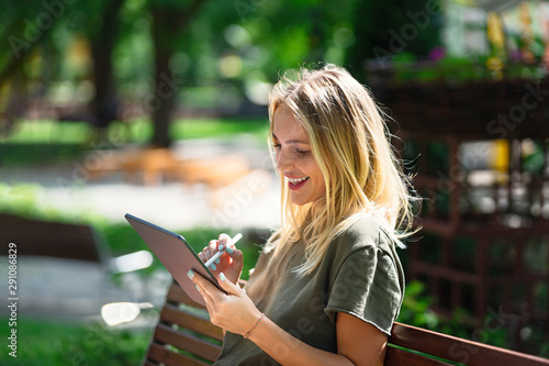 Obraz Young happy smiling woman with tablet on the bench - fototapety do salonu