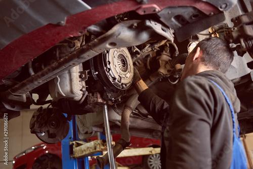 Pinturas sobre lienzo  Back view of man fixing car in repair station