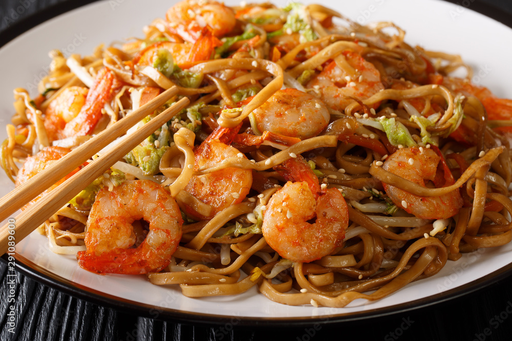 Fototapety, obrazy: Tasty chow mein noodles with shrimp, vegetables and sesame seeds close-up on a plate on the table. horizontal
