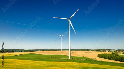 Flying above big wind turbine on field in sunny Poland Obraz na płótnie
