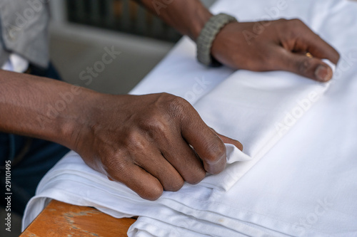 Stampa su Tela  Waiter folds napkins in restaurant