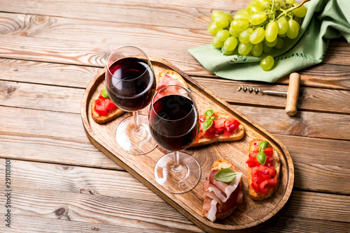 Photo sur Toile Amsterdam Two glasses of red wine, prosciutto and bruschetta, appetizer set on wooden tray, wooden rusitc background