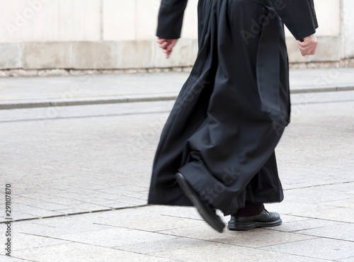 Fototapeta Catholic priest in the black cassock walking on the street solo, only legs visible