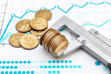 Vernier Caliper With Coins On Business Chart And Graph. Business And Financial Concept.