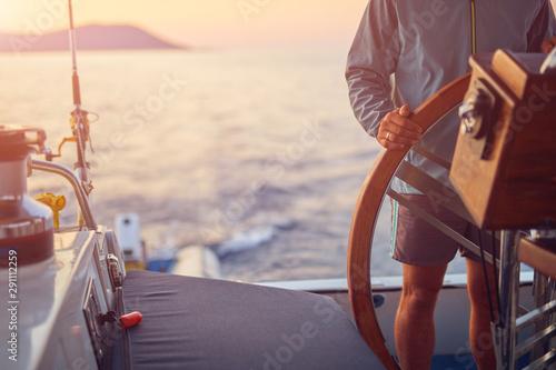 Sailor using wheel to steer rudder on a sailing boat. Obraz na płótnie