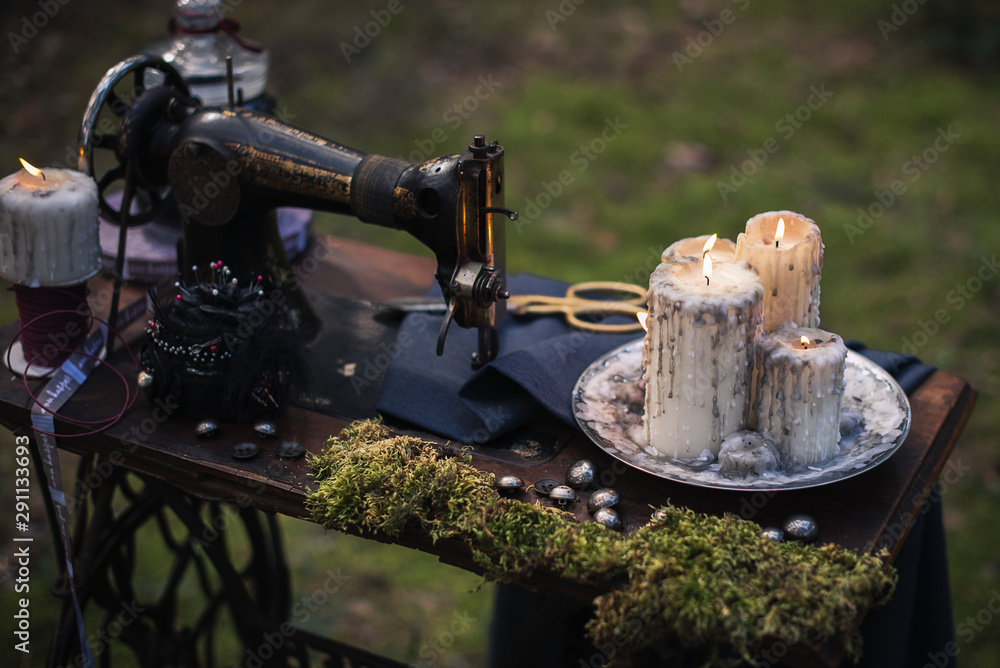 Fototapety, obrazy: an old sewing machine with moss and burning candles outdoors